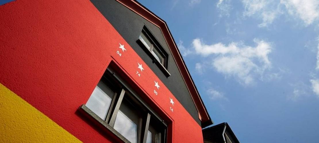 Haus in schwarz, rot, gold