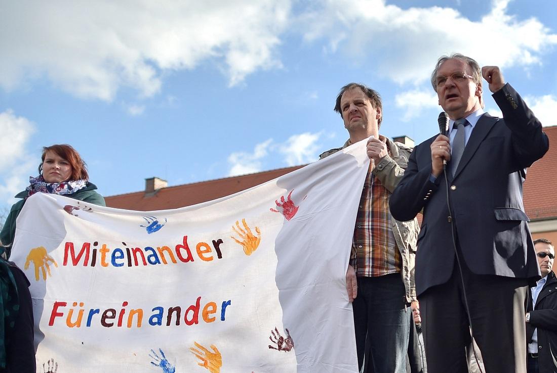 Kurz nach dem Brand kamen Menschen in Tröglitz zusammen, um zu zeigen, dass sie nicht gegen Flüchtlinge sind. Auf dem Foto ist zum Beispiel Sachsens-Anhalts Ministerpräsident Reiner Haseloff (rechts) zu sehen. (Foto: dpa)