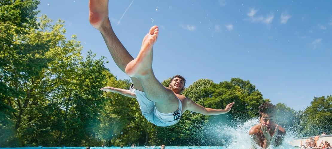 Schadi (16, l) und Yasin (15) springen am 01.07.2015 in Berlin im Schwimmbad ins Wasser. Am Mittwoch und Donnerstag steigen die Temperaturen auf bis zu 36 Grad wie der Deutsche Wetterdienst am Mittwoch in Offenbach berichtete. Meteorologen rechnen für Samstag lokal mit bis zu 39 Grad. Foto: Florian Gaertner/dpa +++(c) dpa - Bildfunk+++