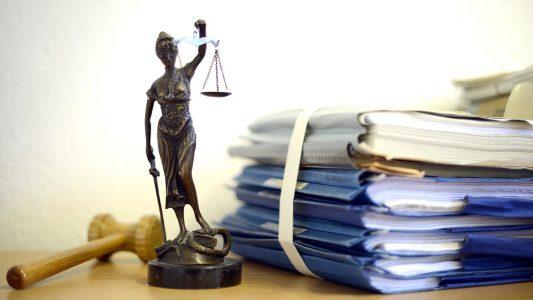 ARCHIV - ILLUSTRATION - Eine modellhafte Nachbildung der Justitia steht am 15.07.2014 im Raum eines Richters des Landgerichts Duisburg (Nordrhein-Westfalen) neben einem Holzhammer und einem Aktenstapel. Im Landgericht Bochum sollen Richter nun das Urteil gegen zwei Männer sprechen, die einen Autoverkäufer umgebracht haben sollen. Die Staatsanwaltschaft hatte für sie lebenslange Haft beantragt. (zu dpa vom 09.01.2018) Foto: Volker Hartmann/dpa +++(c) dpa - Bildfunk+++