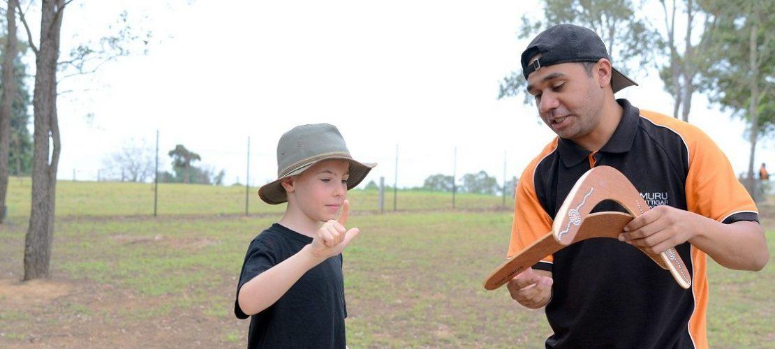 Josh Nicholls erklärt Billy Rosaguti worauf er beim Werfen des Bumerangs achten muss. (Foto: dpa)