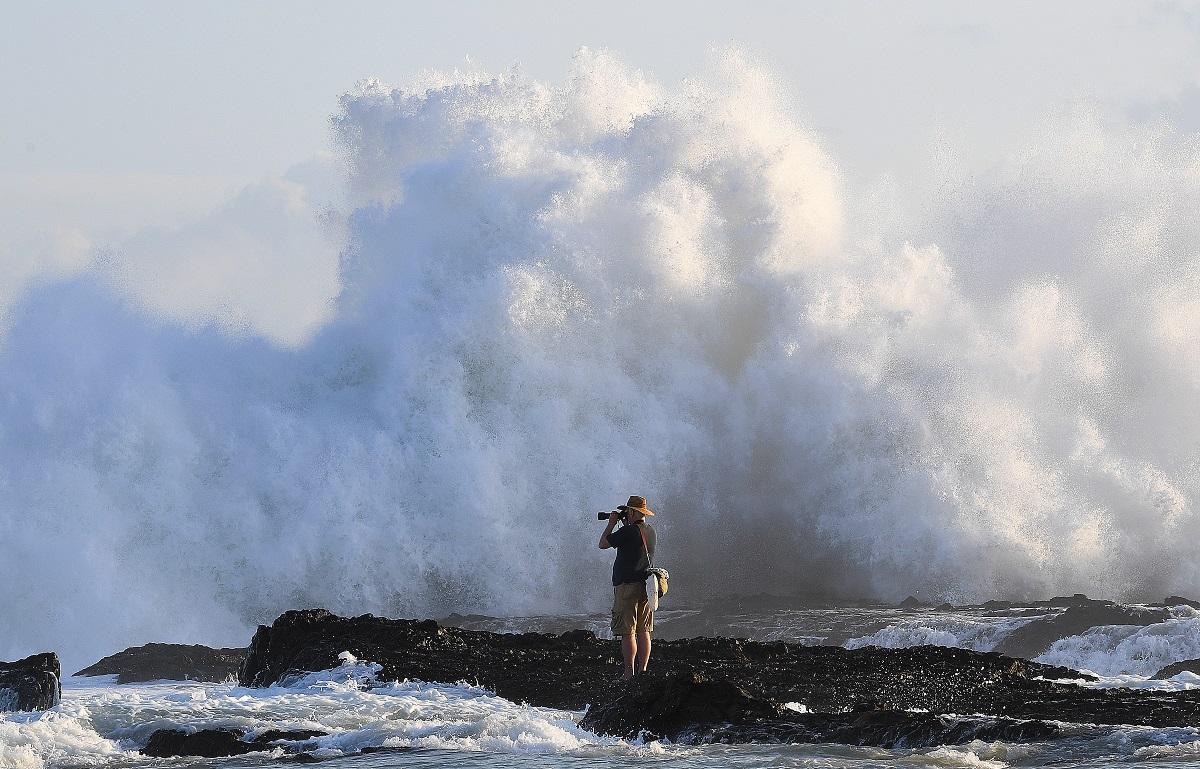 dpatopbilder - 17.02.2018, Australien, Queensland, Gold Coast: Ein Fotograf wartet nahe den Snapper Rocks vor der Brandung auf den richtigen Augenblick. (Foto: Dave Hunt/AAP/dpa)