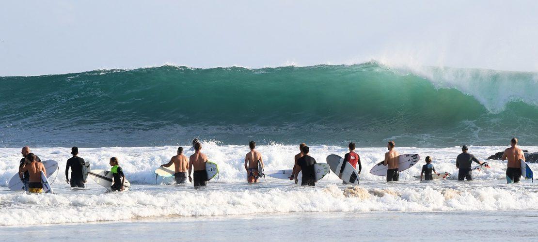 17.02.2018, Australien, Queensland, Gold Coast: Wellenreiter stehen nahe den Snapper Rocks vor der Brandung. Die großen Wellen des Pazifik an der Ostküste sind auch ein Ergebnis des Tropen-Sturms Gita, der vor wenigen Tagen auf den Inseln von Tonga Zerstörungen anrichtete. Surfer freuten sich über hohe Wellen an der Ostküste von Australien. ACHTUNG: Dieses Bild hat dpa auch im Bildfunk gesendet. Foto: Dave Hunt/AAP/dpa - Honorarfrei nur für Bezieher des Dienstes dpa-Nachrichten für Kinder +++ dpa-Nachrichten für Kinder +++