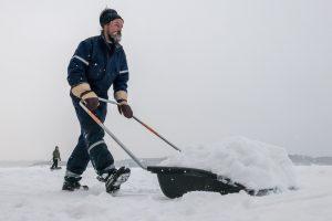Ein Mann schiebt Schnee auf dem Saimaa-See. (Foto: dpa)