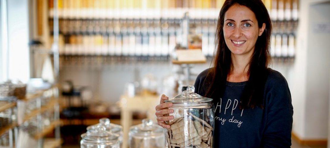 Dinah Stark steht in ihrem Laden. In dem großen Glas in ihrer Hand befinden sich Lebensmittel. (Foto: Thilo Schmülgen)