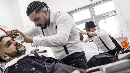Barbier Onay Temel (M) bearbeitet mit einem Rasiermesser den Bart von Sekran (l). (Foto: dpa)