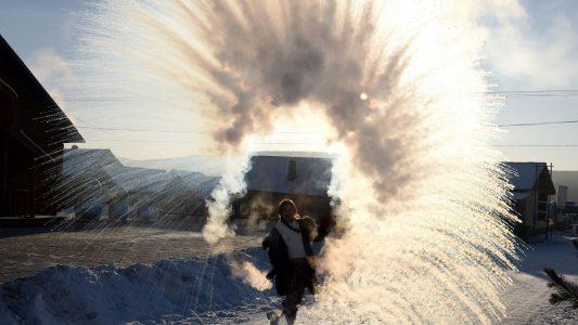 China, Mohe: Eine Touristin sprüht heißes Wasser in die Luft, das unverzüglich gefriert. Foto: Chu Fuchao/SIPA Asia via ZUMA Wire/dpa