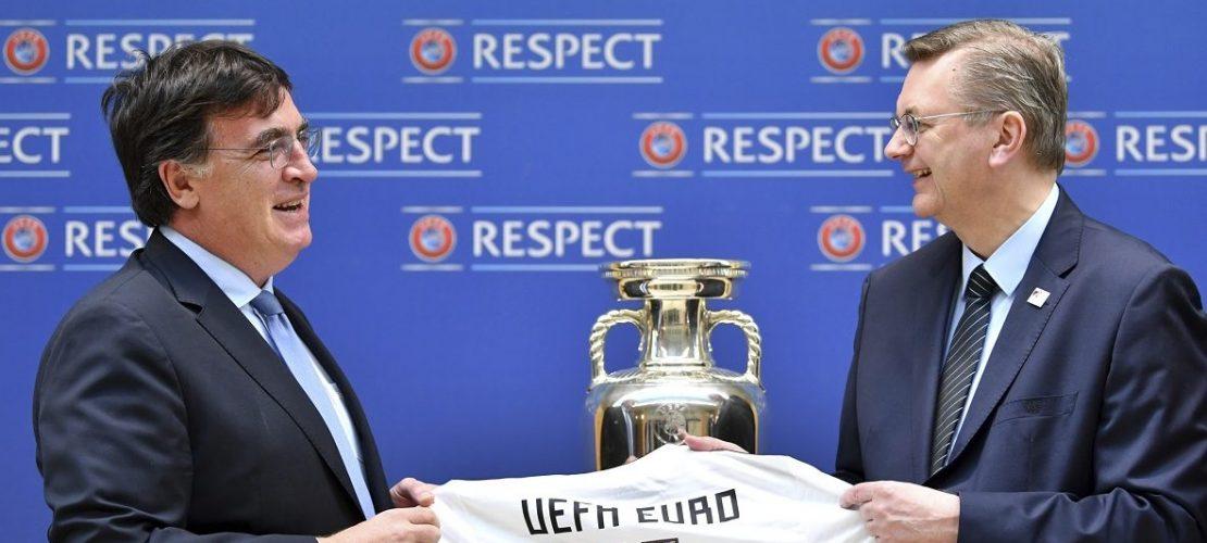 Der Präsident des Deutschen Fußballbundes Reinhard Grindel (r) übergibt die Bewerbungsunterlagen für die EM 2024 an UEFA-Generalsekretär Theodore Theodoridis, sowie ein Trikot mit der Rückennummer UEFA Euro 24. (Foto: dpa)
