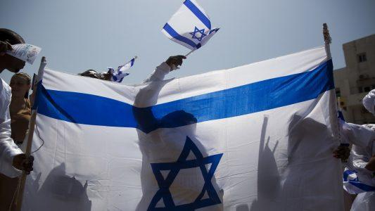 19.04.2018, Israel, Tel Aviv: Ein Feiernder schwenkt eine israelische Flagge hinter einer großen Fahne am 70. Unabhängigkeitstag des jüdischen Staates.