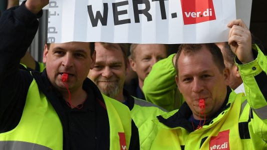 10.04.2018, Bremen: Streikende ver.di Mitarbeiter stehen vor einem Eingang zum Airport Bremen und halten Plakate mit