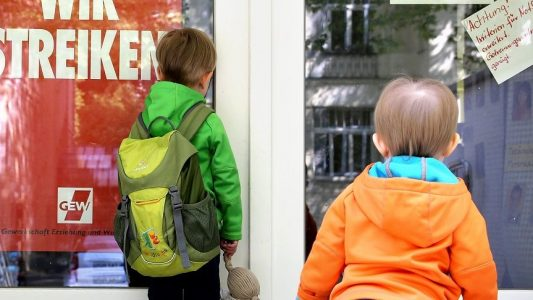 Zwei kleine Kinder stehen am 18.05.2015 an der Tür eines wegen Streik geschlossenen Kindergartens in Leipzig (Sachsen).
