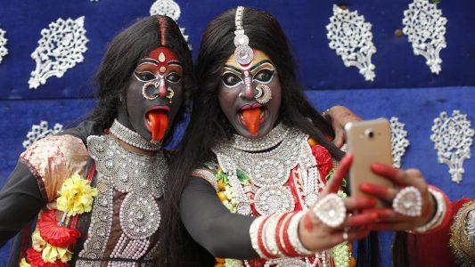 13.02.2018, Indien, Allahabad: Zwei als Hindu-Gottheit Kali verkleidete Jugendliche machen im Rahmen des Shivaratri Festivals ein Selfie.