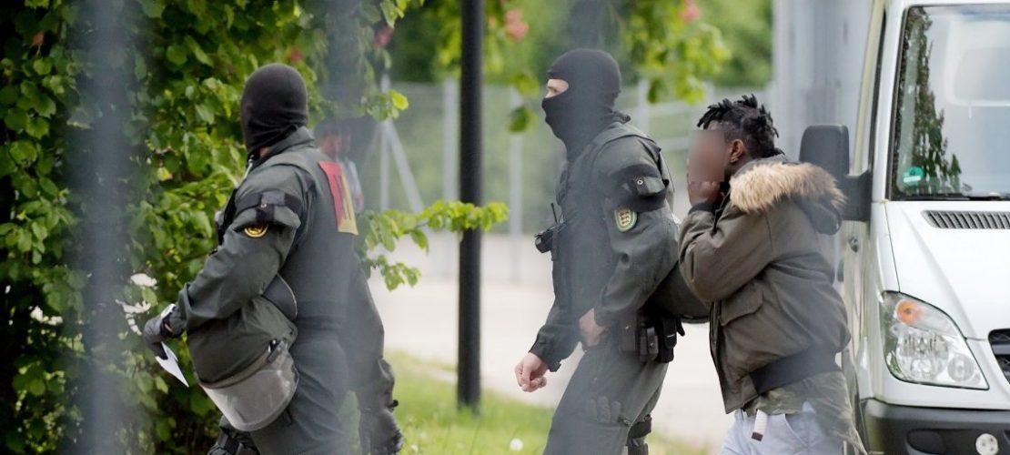 In der Landeserstaufnahmeeinrichtung für Flüchtlinge (LEA) wird ein Mann von maskierten Polizisten eskortiert. (Foto: Stefan Puchner/dpa)