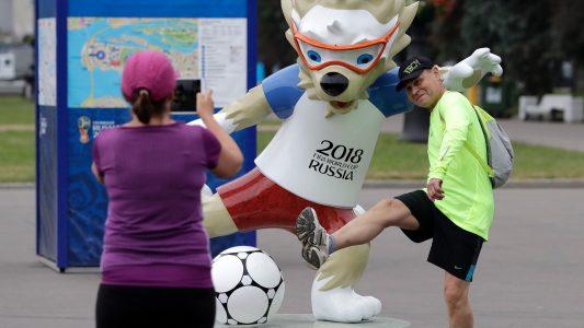 Fußballfans machen vor dem WM-Stadion mit dem Maskottchen, dem Wolf Sabiwaka, ein Erinnerungsfoto. (Foto: Lee Jin-Man/AP/dpa)