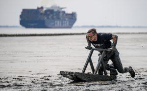 Bis zu den Knien sinken die Sportler im Matsch ein. Mit einem Schlitten geht es etwas besser. Foto: Axel Heimken/dpa
