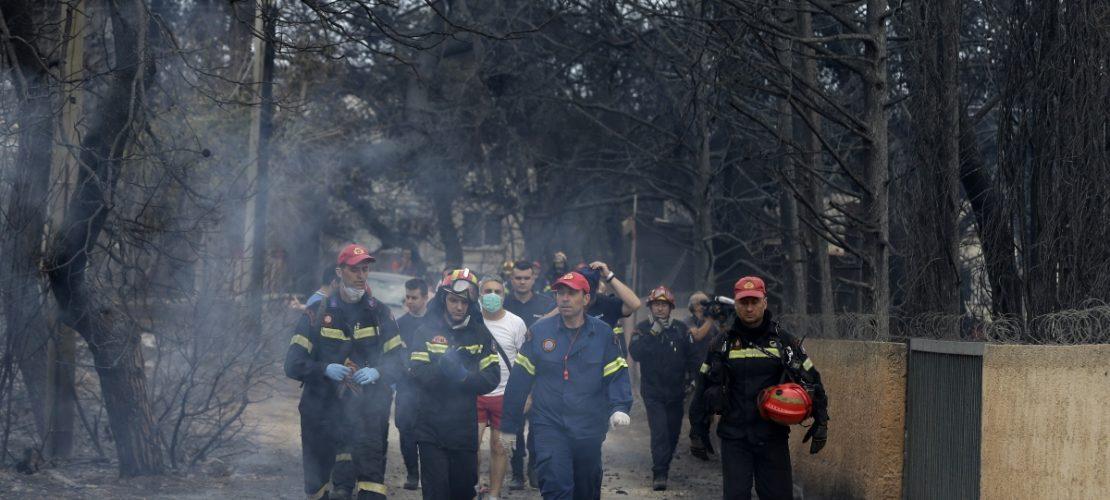 Feuerwehrleute inspizieren ein verbranntes Gebiet. Großbrände nahe Athen haben viele Menschen das Leben gekostet. (Foto: dpa)