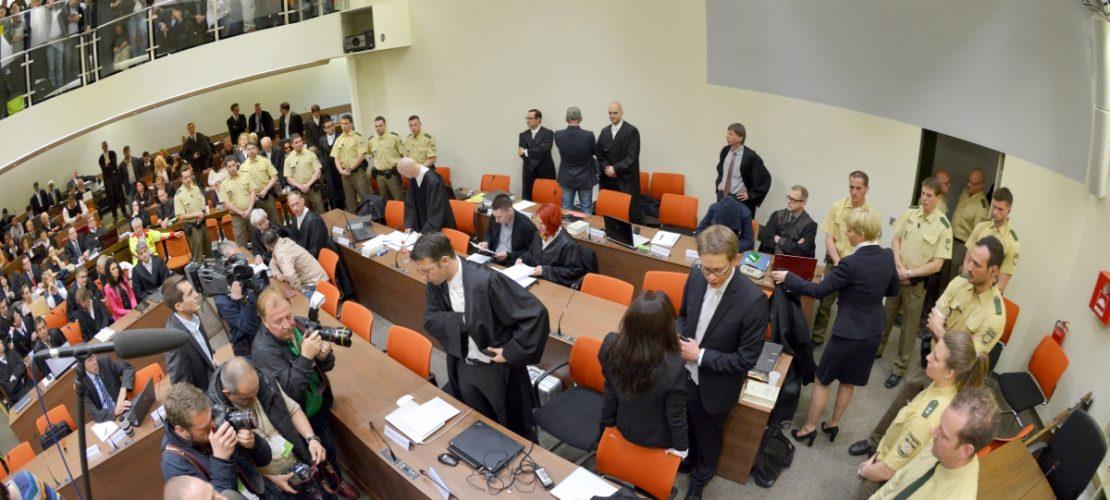 Ein Bild aus dem NSU-Prozess: Die Angeklagte Beate Zschäpe (Gruppe rechts unten in der Mitte) steht vor Beginn des Prozesses im Gerichtssaal München neben ihren Anwälten Wolfgang Stahl (l), Wolfgang Heer und Anja Sturm (r) und dreht den Zuschauern den Rücken zu. (Foto: dpa)