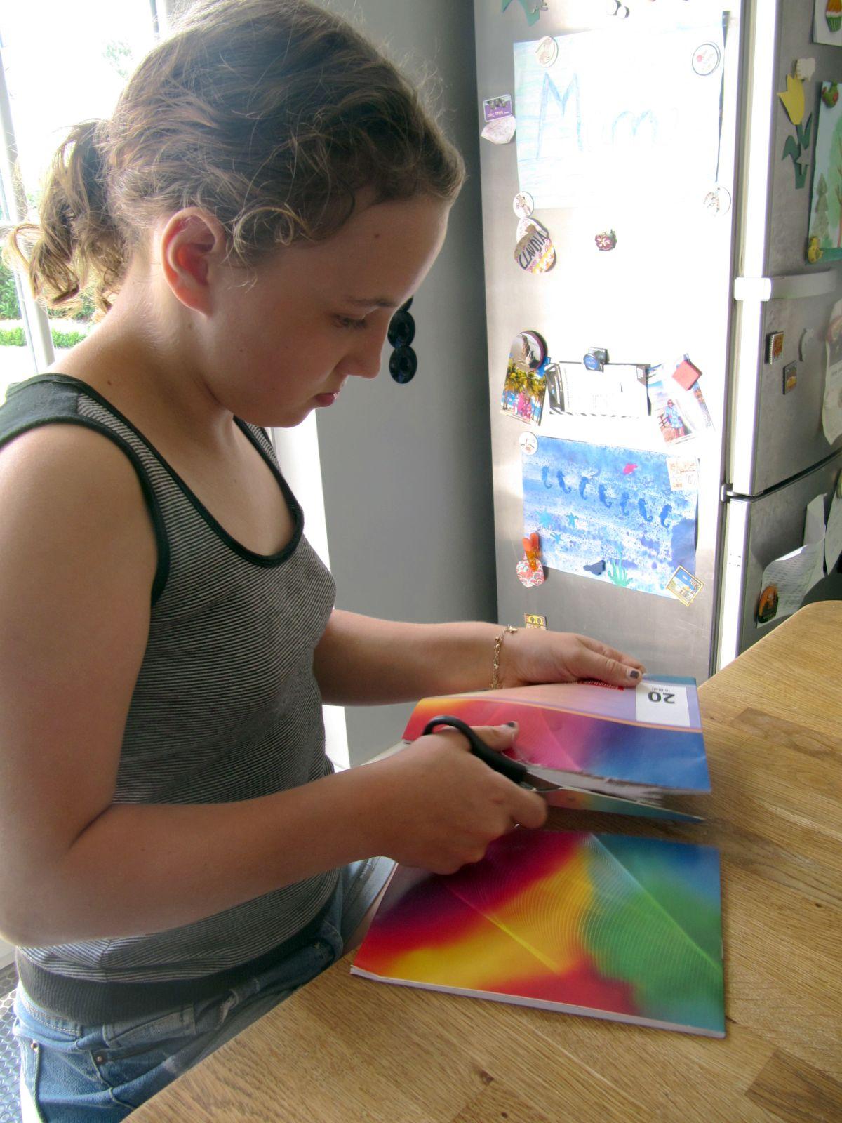 Mia teilt ein übrig gebliebenes Heft. Und schwupps, nun hat sie zwei Schulhefte. (Foto: Claudia Bonati/dpa)