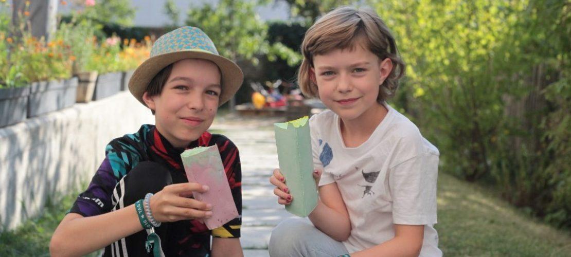 Juli (l) und Tilda (r) freuen sich über die selbst gemachte Straßenkreide. Foto: Corinna Schwanhold/dpa