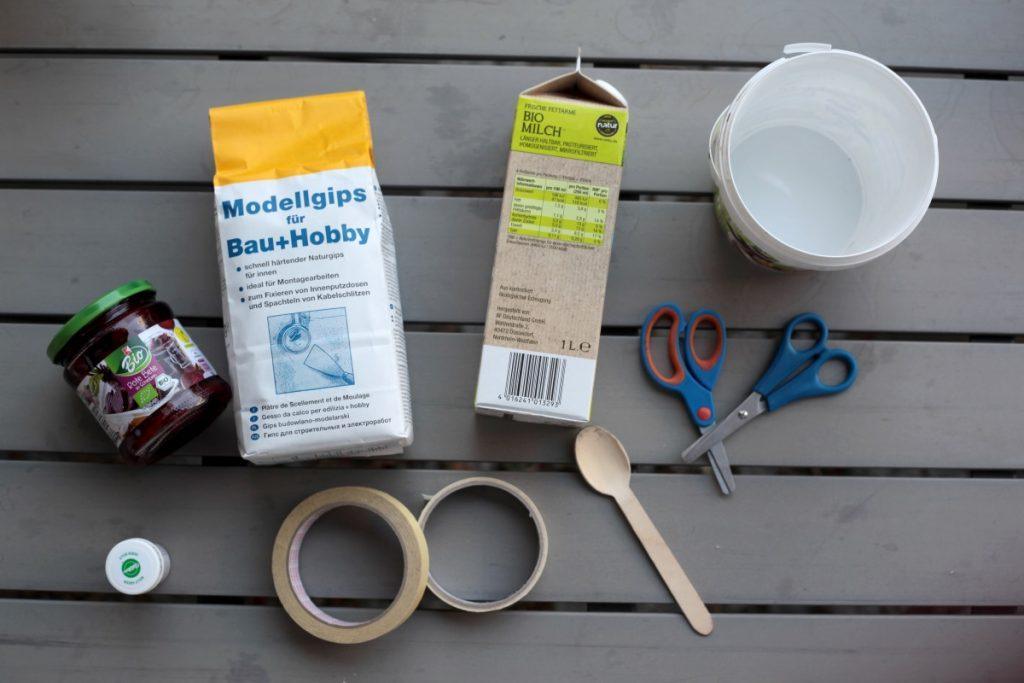 Die Materialien für Straßenkreide: Gips, Lebensmittelfarbe, ein Eimer zum Umrühren, Klebeband, Tetrapak. Straßenkreide kann man aus wenigen Materialien selbst herstellen. Foto: Corinna Schwanhold/dpa